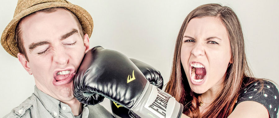 Woman wearing boxing glove, pretending to knock a man out