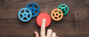 Colorful plastic cogs being repositioned by someone's hand
