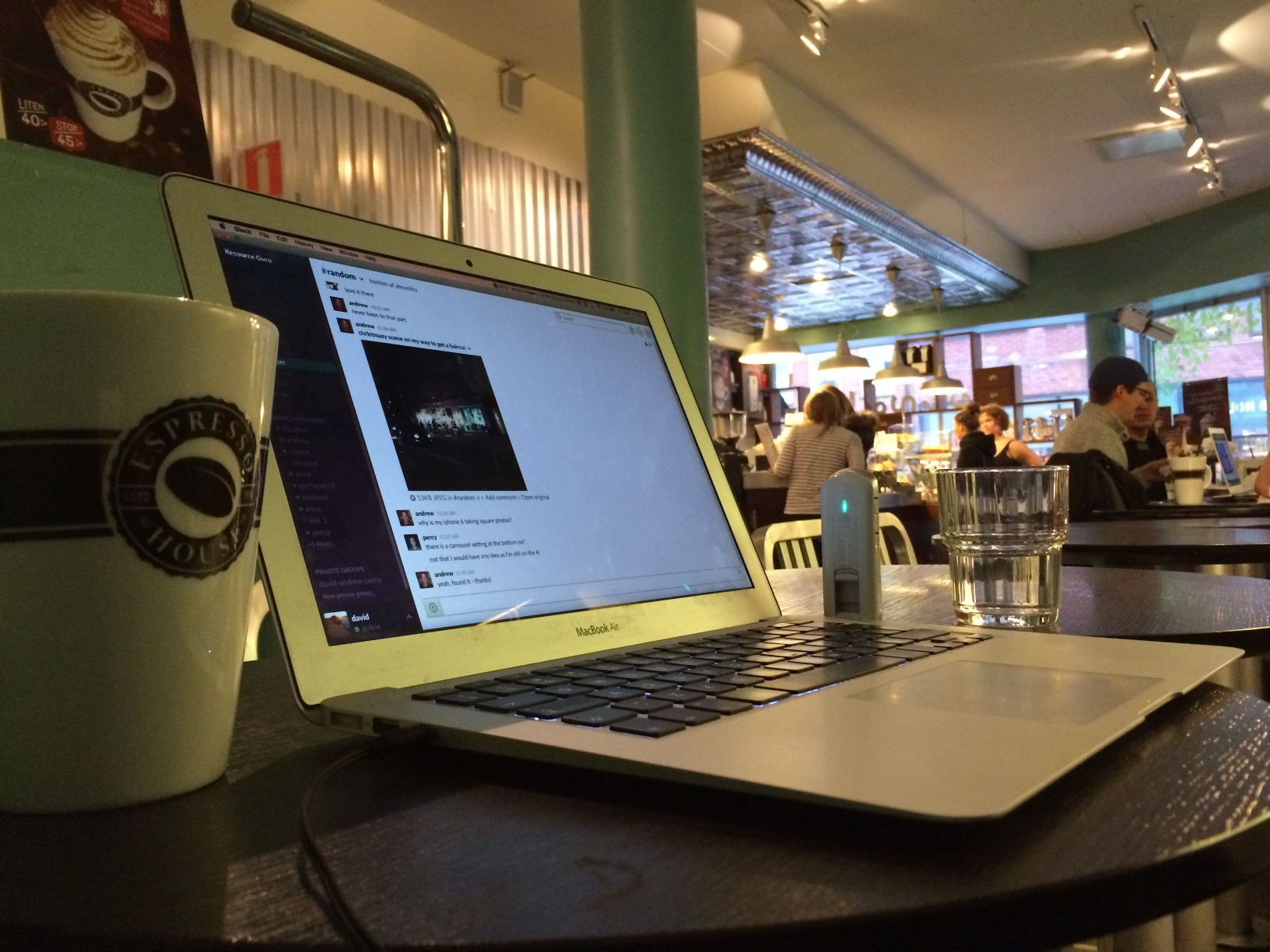 Laptop and coffee cup on table at bistro