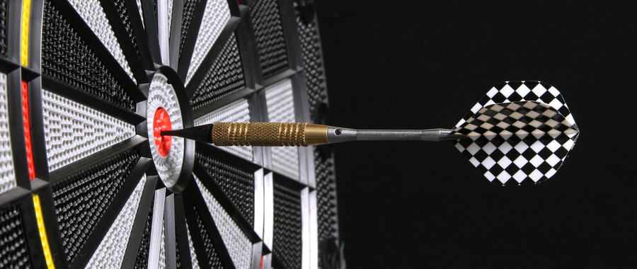 Closeup shot of dartboard, with a dart lodged in the bullseye